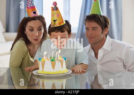 Boy Blowing out Birthday Candles avec les parents Banque D'Images