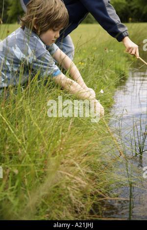 Garçons jouant dans l'étang