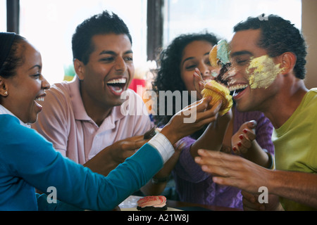 Les amis ayant Food Fight in Restaurant Banque D'Images