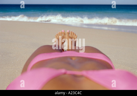 Young woman in pink bikini lying on beach Banque D'Images