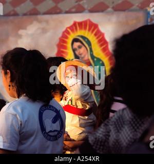 Les jeunes enfants étant photographiés devant la Vierge Guadalupe au fiesta du jour de la Vierge Mazatlan Mexique Banque D'Images