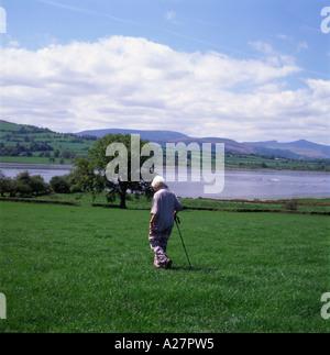 Personnes âgées senior woman with wallking stick avec une vue sur le lac de Llangorse Brecon Beacons et la montagne Banque D'Images