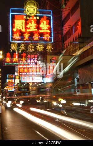 Sentier de la lumière d'un autobus qui passe des enseignes au néon floue sur Nathan Road, Kowloon Hong Kong Banque D'Images