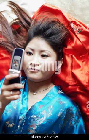 High angle view of a young woman lying on her back holding a mobile phone Banque D'Images