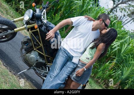 Couple à moto et s'embrasser sur route Banque D'Images