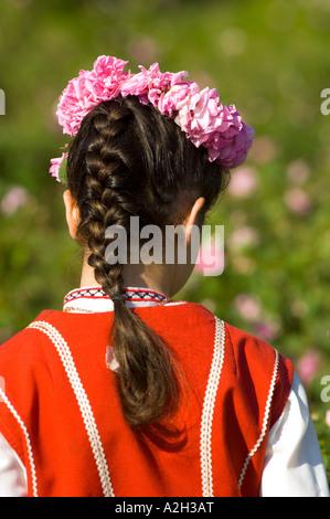 Jeune femme dans le champ de rosiers habillé en robe folk traditionnel bulgare pendant la récolte des pétales de Banque D'Images