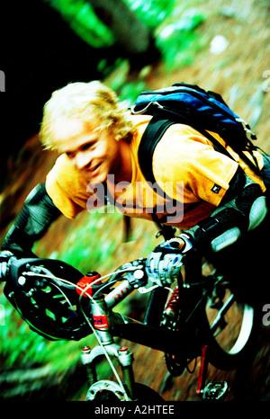 Âge d'hommes 20-25 équitation un vélo de montagne à travers les bois. L'image montre le mouvement et n'est en couleur. Banque D'Images