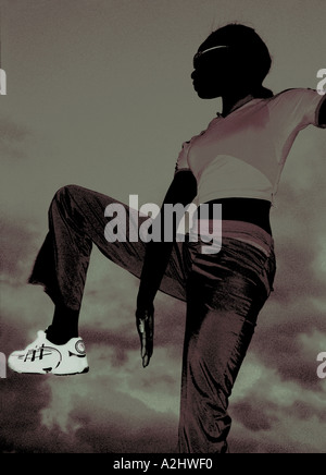 Black femme âge 20-25 portant des vêtements de sport, l'image est tourné au crépuscule contre le ciel en Espagne. Banque D'Images