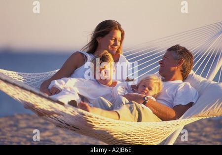 Père et mère de leurs deux enfants couchés ensemble dans un hamac sur la plage Banque D'Images