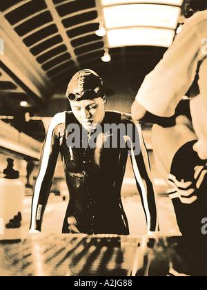 L'âge des femelles,nageur 20-25 sortant d'une piscine avec son entraîneur au premier plan. Banque D'Images