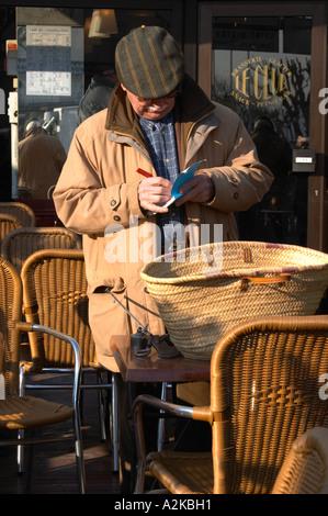 Homme vente achat truffes au marché aux truffes de Carpentras. Noter quelque chose sur un ordinateur portable et avec une échelle et un sac de transport sur la table devant lui. Carpentras, Vaucluse, France, Europe