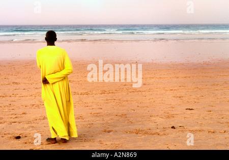 L'homme en robe jaune et des tongs les regards vers la mer au nord de Dakar Yoff Sénégal Banque D'Images