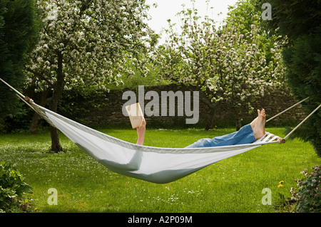 Woman in hammock reading book Banque D'Images
