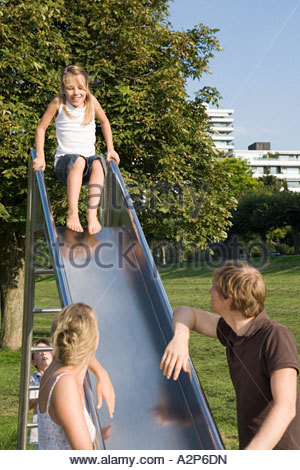 Family playing on slide Banque D'Images