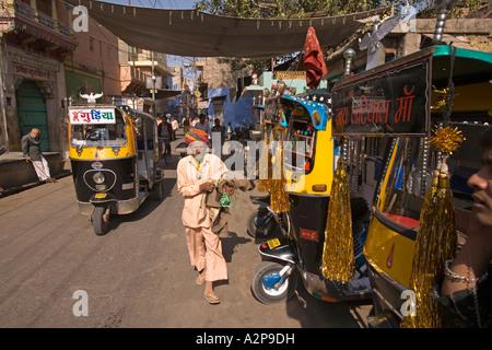 Inde Rajasthan Jodhpur vieille ville man walking passé auto rickshaws décorées Banque D'Images