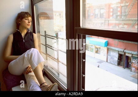 Woman sitting on windowsill Banque D'Images