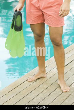 Homme debout en bord de piscine, tenant des palmes, taille en bas Banque D'Images