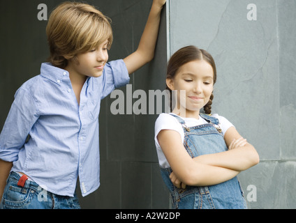 Garçon et fille, boy leaning against wall, girl crossing arms Banque D'Images