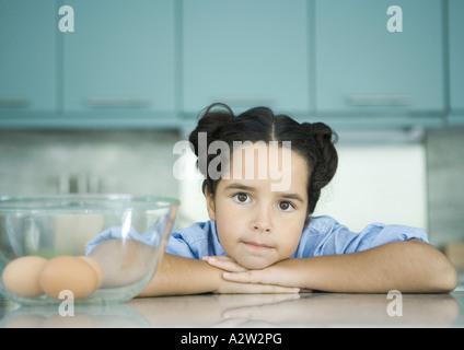 Girl resting head on compteur à côté bol contenant des œufs Banque D'Images