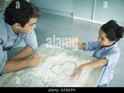 Père et fille Ensemble de cuisson, cœur dessiné dans la farine sur le comptoir Banque D'Images