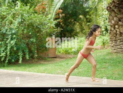 Fille en maillot de bain s'exécutant en arrière-cour Banque D'Images