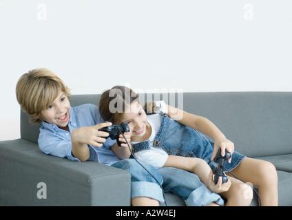 Des enfants assis sur le canapé, tenant les leviers de Banque D'Images