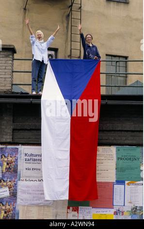 Deux filles forme aux côtés du drapeau national lors de la révolution de 1998 à Prague. Banque D'Images