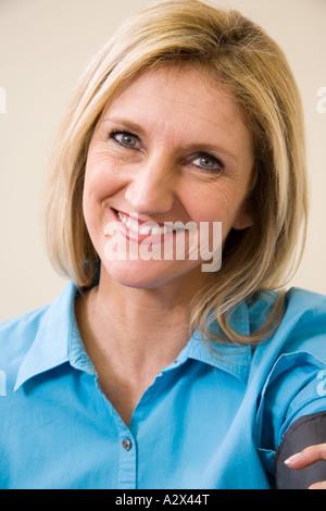 Patient de sexe féminin ayant sa pression artérielle mesurée (prises) pendant un examen. Banque D'Images