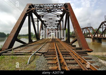 Pont de chemin de fer rouille traversant une large rivière Banque D'Images