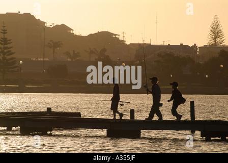 Trois garçons sur une jetée à la pêche au coucher de soleil doré découpé sur la tenue des cannes à pêche l'ouest Banque D'Images