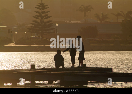Trois garçons sur une jetée à la pêche au coucher de soleil doré découpé sur Holiding cannes à pêche l'ouest de Banque D'Images