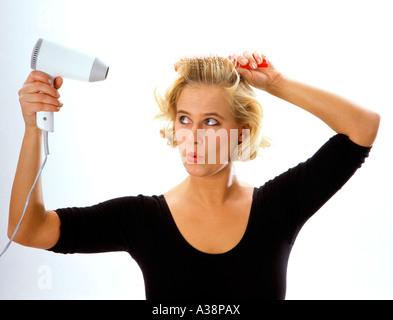 Frau foehnt sich die Haare, portrait de femme cheveux séchage par hairblower Banque D'Images
