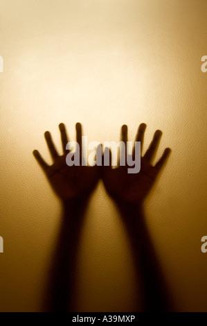 Deux mains derrière la vitre Banque D'Images