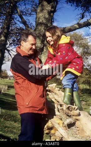 Jeune fille avec son père, escalade un tronc d'arbre tombé dans la campagne Banque D'Images