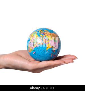 Main de femme tendue avec un globe posé sur le repose sur un fond blanc.