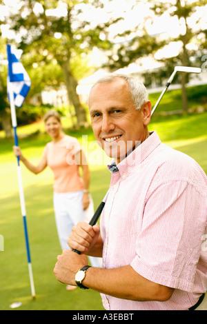 Portrait of a young man holding a golf club et a young woman holding a golf drapeau dans l'arrière-plan Banque D'Images
