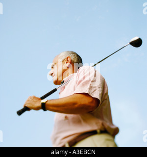 Low angle view of a young man holding a golf club Banque D'Images