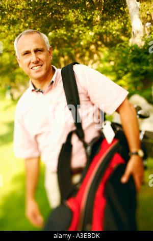 Portrait d'un homme mûr portant un sac de golf et smiling Banque D'Images