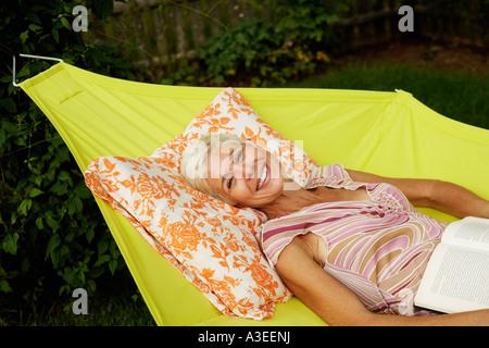 Portrait of a senior woman couché dans un hamac et souriant