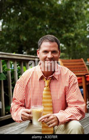 Portrait of a businessman holding a mug de milkshake et smiling
