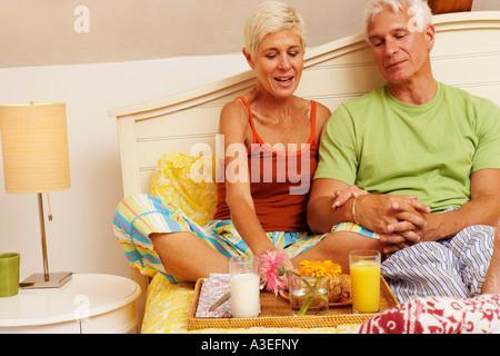 Homme mature et a senior woman assis sur le lit et le petit déjeuner Banque D'Images