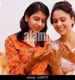Portrait de deux jeunes femmes à la recherche de leurs mains tatouées au henné Banque D'Images