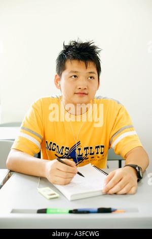 Jeune homme assis dans la classe et de l'écoute d'un MP3 player Banque D'Images