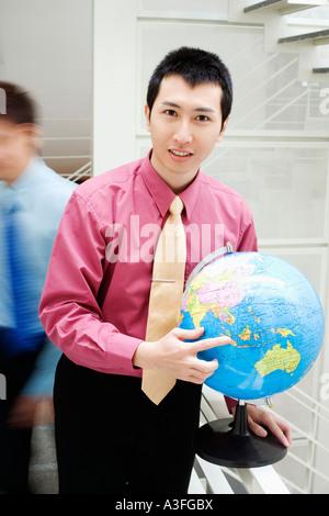 Portrait of a businessman holding a globe