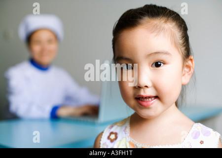 Portrait d'une fille et d'une infirmière qui travaille sur un ordinateur portable à l'arrière-plan