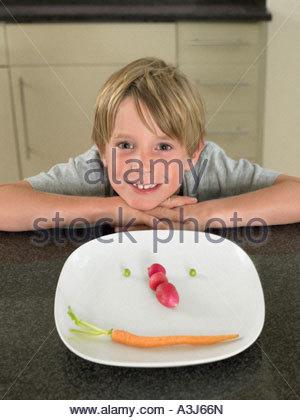 Garçon avec face de légumes sur une plaque Banque D'Images