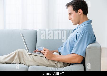 L'homme à l'aide d'un ordinateur portable à la maison Banque D'Images