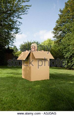 Garçon dans une boîte en carton Banque D'Images