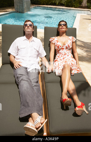 Couple Relaxing by Pool Banque D'Images