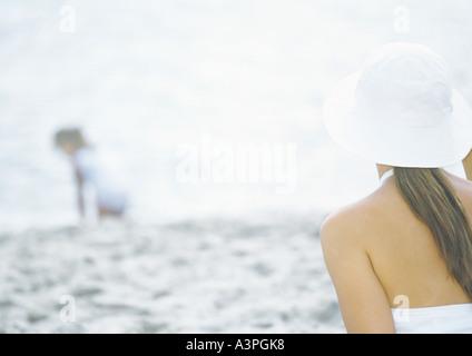 Mère de l'enfant regardant on beach Banque D'Images